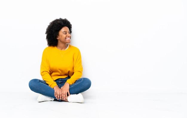 Młoda african american kobieta siedzi na podłodze patrząc z boku