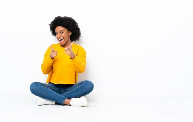 Młoda african american kobieta siedzi na podłodze, wskazując do przodu i uśmiechając się