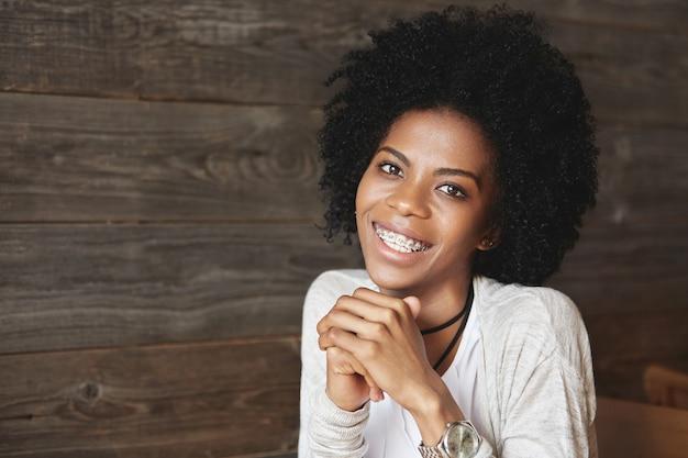 Młoda african-american kobieta siedzi w kawiarni