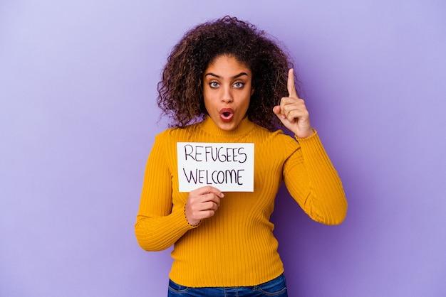 Młoda african american kobieta trzyma afisz powitalny uchodźców na białym tle pomysł, koncepcja inspiracji.