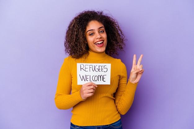 Młoda african american kobieta trzyma afisz powitalny uchodźców na białym tle radosny i beztroski przedstawiający symbol pokoju palcami.