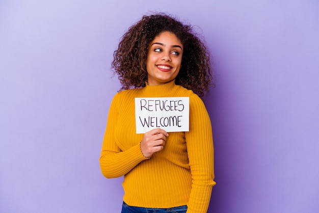 Młoda african american kobieta trzyma afisz powitalny uchodźców na białym tle wygląda na bok uśmiechnięty, wesoły i przyjemny.