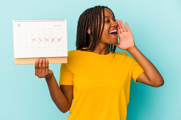 Młoda african american kobieta trzyma kalendarz na białym tle na niebieskim tle krzycząc i trzymając dłoń w pobliżu otwarte usta.