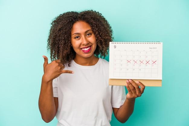 Młoda african american kobieta trzyma kalendarz na białym tle na niebieskim tle pokazując gest połączenia z telefonu komórkowego palcami.