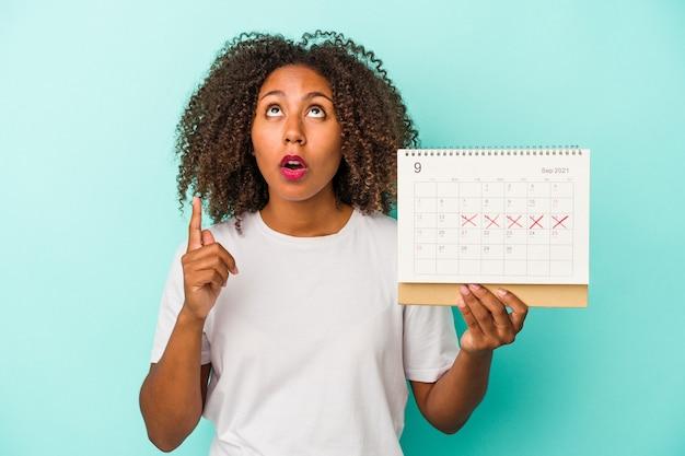 Młoda african american kobieta trzyma kalendarz na białym tle na niebieskim tle, wskazując do góry z otwartymi ustami.