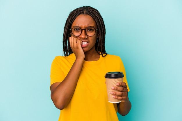 Młoda african american kobieta trzyma kawę na wynos na białym tle na niebieskim tle gryzie paznokcie, nerwowa i bardzo niespokojna.