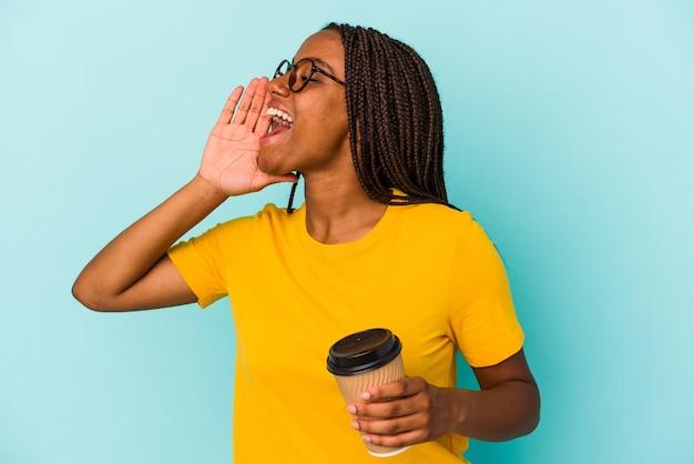 Młoda african american kobieta trzyma kawę na wynos na białym tle na niebieskim tle krzycząc i trzymając dłoń w pobliżu otwartych ust.