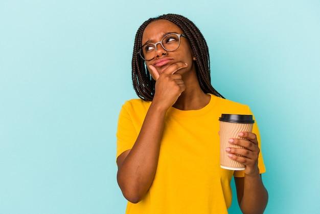 Młoda african american kobieta trzyma kawę na wynos na białym tle na niebieskim tle, patrząc w bok z wyrazem wątpliwości i sceptycyzmu.