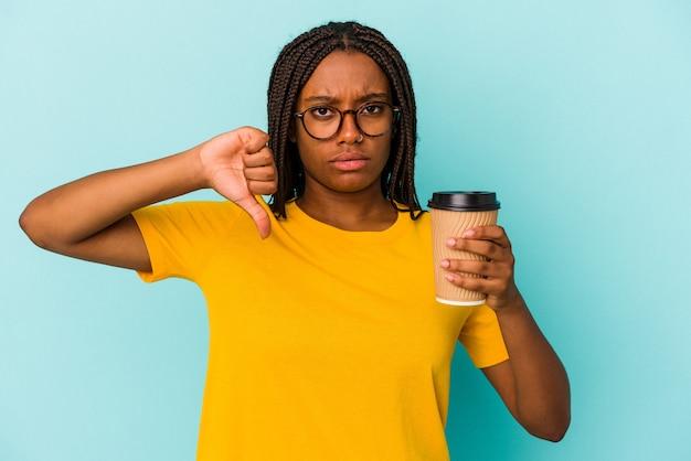 Młoda african american kobieta trzyma kawę na wynos na białym tle na niebieskim tle pokazując gest niechęci, kciuk w dół. koncepcja niezgody.