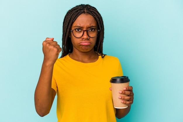 Młoda african american kobieta trzyma kawę na wynos na białym tle na niebieskim tle pokazując pięść do kamery, agresywny wyraz twarzy.
