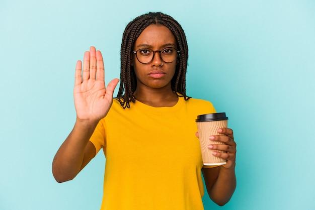 Młoda african american kobieta trzyma kawę na wynos na białym tle na niebieskim tle stojąc z wyciągniętą ręką pokazując znak stop, uniemożliwiając.