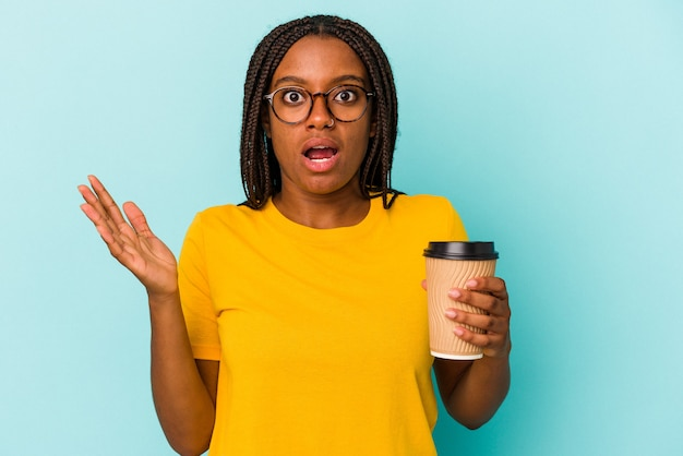 Młoda african american kobieta trzyma kawę na wynos na białym tle na niebieskim tle zaskoczony i zszokowany.
