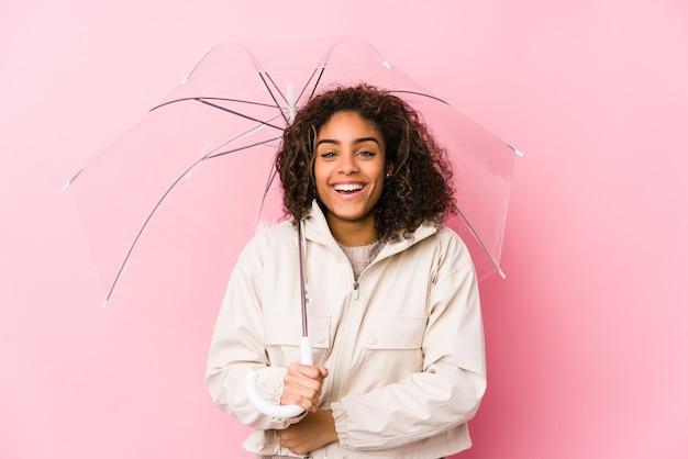 Młoda african american kobieta trzyma parasol, śmiejąc się i zabawę