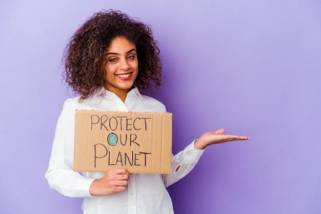 Młoda african american kobieta trzyma tabliczkę moc dziewczyna na białym tle na fioletowym tle przedstawiający miejsce na kopię na dłoni i trzymając drugą rękę na talii.