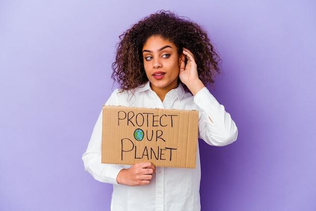 Młoda african american kobieta trzyma tabliczkę moc dziewczyna na fioletowym próbując słuchać plotek.