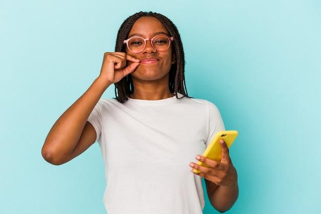Młoda african american kobieta trzyma telefon komórkowy na białym tle na niebieskim tle z palcami na ustach zachowując tajemnicę.