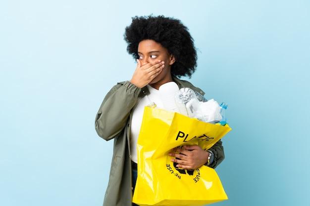 Młoda african american kobieta trzyma torbę kosza, robi gest niespodzianki, patrząc z boku