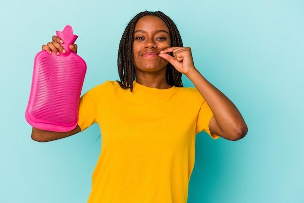 Młoda african american kobieta trzyma worek gorącej wody na białym tle na niebieskim tle z palcami na ustach, zachowując tajemnicę.