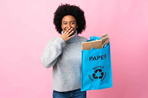 Młoda african american kobieta trzyma worek kosza na białym tle na kolorowe usta stożka szczęśliwy i uśmiechnięty ręką