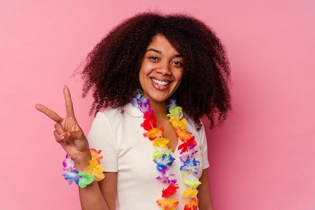 Młoda african american kobieta ubrana w hawajskie rzeczy pokazujące numer dwa palcami.