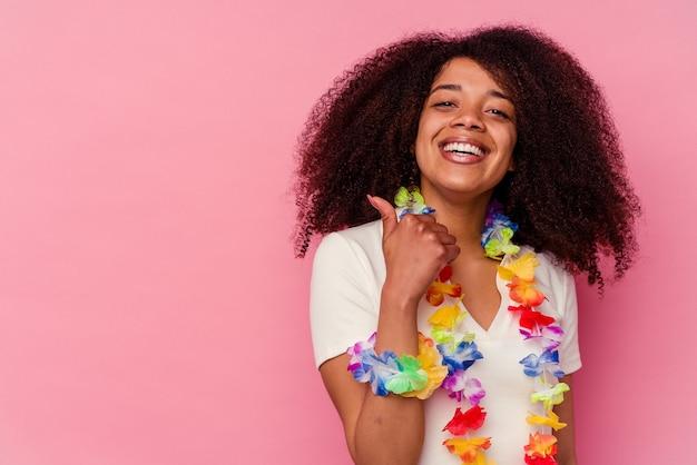 Młoda african american kobieta ubrana w hawajskie rzeczy, uśmiechając się i podnosząc kciuk do góry