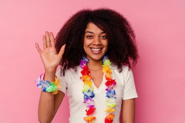 Młoda african american kobieta ubrana w hawajskie rzeczy uśmiechający się wesoły, pokazując numer pięć palcami.