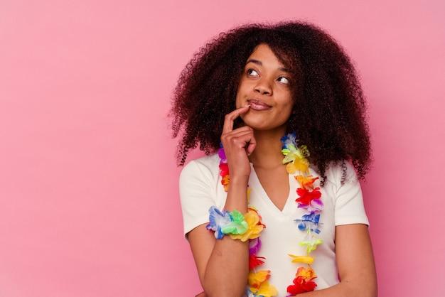 Młoda african american kobieta ubrana w hawajskie rzeczy zrelaksowany, myśląc o czymś, patrząc na przestrzeń kopii.