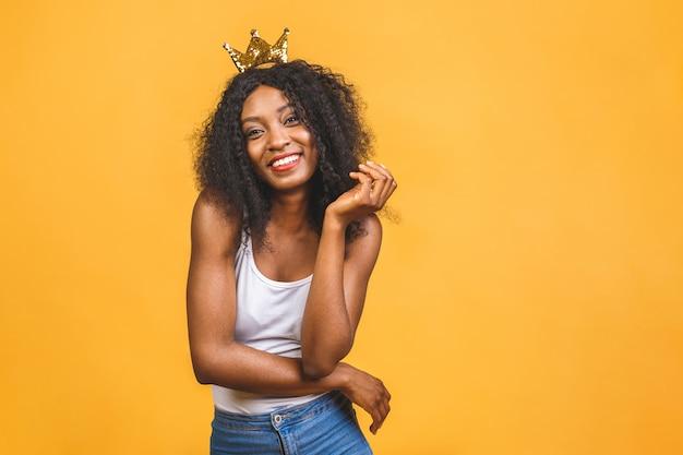 Młoda african american kobieta ubrana w złotą koronę królowej z radosnym i chłodnym uśmiechem na twarzy