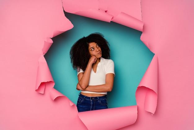 Młoda african american kobieta w rozdartym papierze na białym tle na niebieskim tle, która czuje się smutna i zamyślona, patrząc na miejsce.