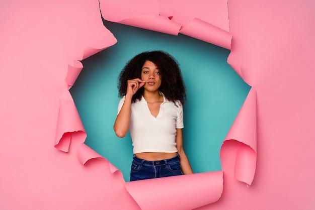 Młoda african american kobieta w rozdartym papierze na białym tle na niebiesko z palcami na ustach dochowując tajemnicy.