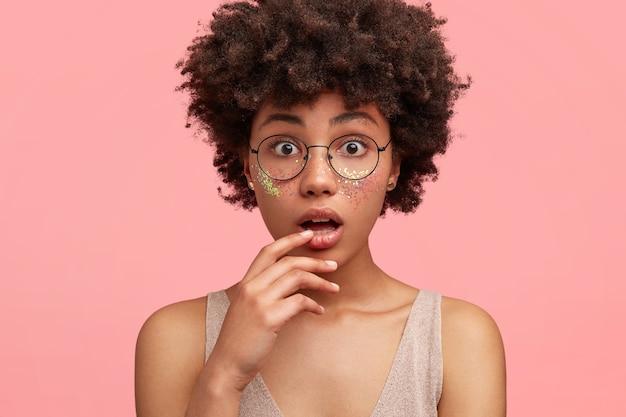 Młoda african-american kobieta z brokatem na twarzy