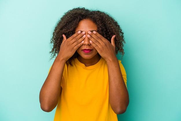 Młoda african american kobieta z kręconymi włosami na białym tle na niebieskim tle boi się zasłaniając oczy rękami.