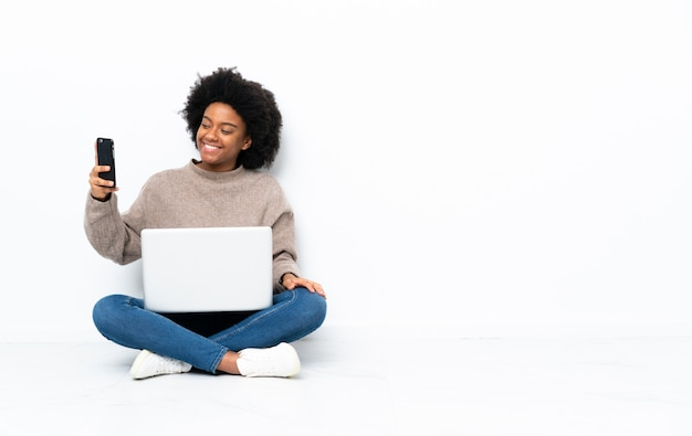 Młoda african american kobieta z laptopem siedząc na podłodze, dzięki czemu selfie