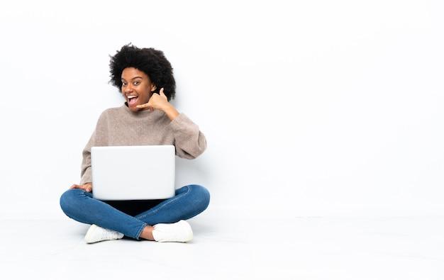 Młoda african american kobieta z laptopem siedząc na podłodze gest telefonu. oddzwoń do mnie znak