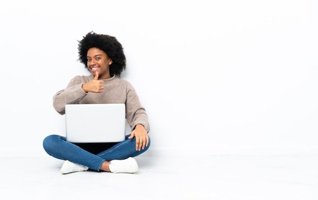 Młoda african american kobieta z laptopem siedzi na podłodze, dając kciuk do góry gestu