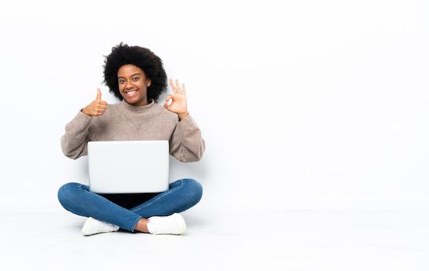 Młoda african american kobieta z laptopem siedzi na podłodze, pokazując znak ok i kciuk w górę gestu