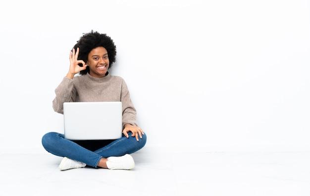 Młoda african american kobieta z laptopem siedzi na podłodze, pokazując znak ok palcami