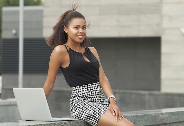 Młoda african american kobieta za pomocą laptopa na schodach na zewnątrz