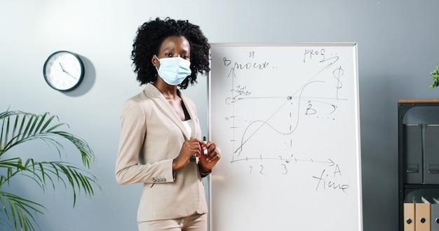 Młoda african american nauczycielka kobieta w masce medycznej stojącej na pokładzie w klasie i mówiąca klasie prawa fizyki lub geometrii. koncepcja pandemii. szkoła podczas koronawirusa. wykład wychowawczy.