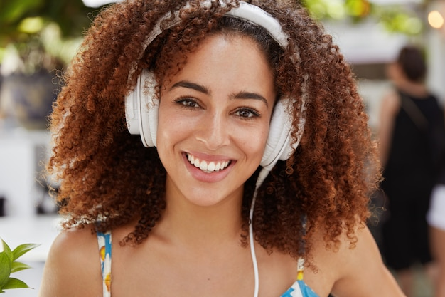 Młoda african american szczęśliwa kobieta cieszy się doskonałym dźwiękiem, słuchając muzyki w nowoczesnych słuchawkach