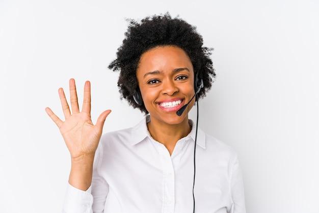 Młoda african american telemarketer kobieta na białym tle uśmiechnięty wesoły pokazując numer pięć palcami.