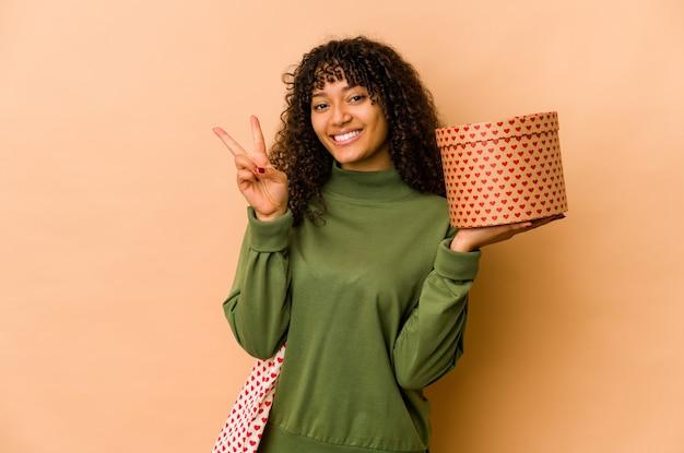 Młoda afro afro kobieta afroamerykanów gospodarstwa prezent walentynki pokazując numer dwa palcami.