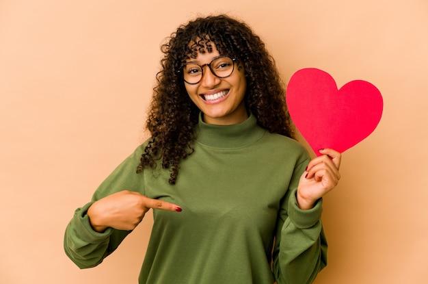 Młoda afro amerykanka afro kobieta trzyma serce walentynki osoba, wskazując ręką na przestrzeni kopii koszuli, dumna i pewna siebie