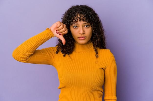 Młoda afro amerykańska kobieta afro na białym tle pokazująca niechęć gest, kciuk w dół. pojęcie sporu.