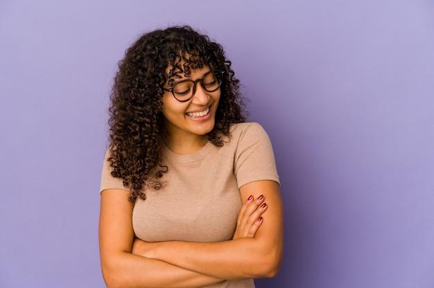 Młoda afro amerykańska kobieta afro na białym tle uśmiechnięty pewnie ze skrzyżowanymi rękami.