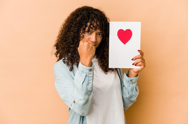 Młoda afro amerykańska kobieta afro trzyma kartę walentynki pokazując pięść do kamery, agresywny wyraz twarzy.
