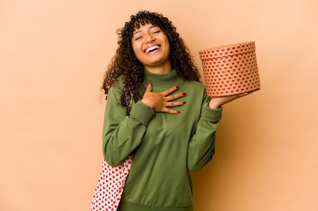 Młoda afro amerykańska kobieta afro trzyma prezent walentynki śmieje się głośno, trzymając rękę na piersi.