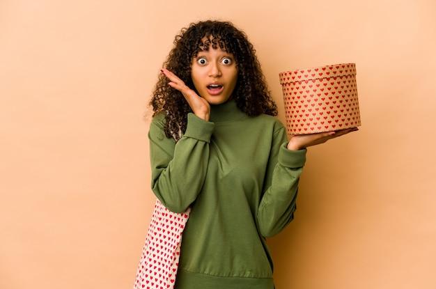 Młoda afro amerykańska kobieta afro trzyma prezent walentynki zaskoczony i zszokowany.