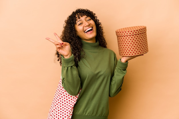 Młoda afro amerykańska kobieta afro trzymająca prezent walentynkowy radosny i beztroski pokazujący palcami symbol pokoju.