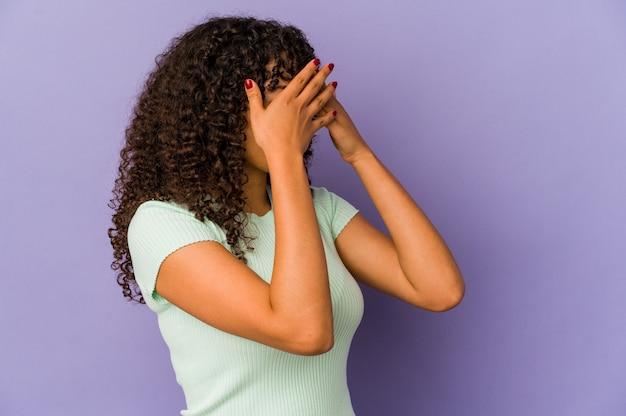 Młoda afro amerykańska kobieta na białym tle przestraszony obejmujące oczy rękami.